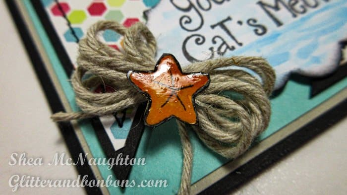 Close up of tiny stamped, colored starfish image with twine bow behind it