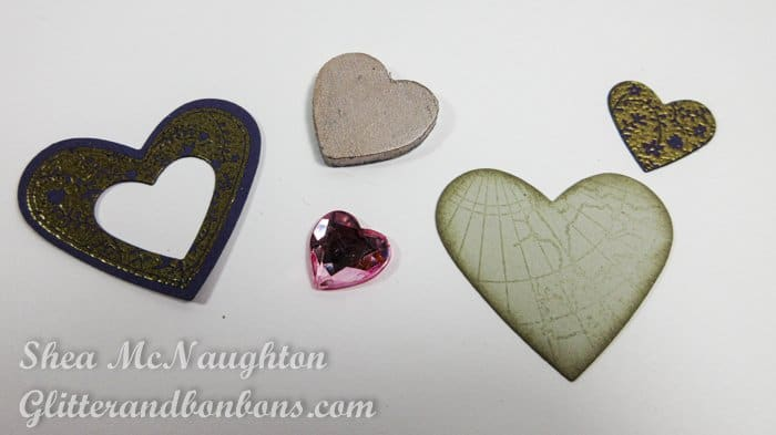 5 hearts of different materials, including paper, wood and a plastic gem