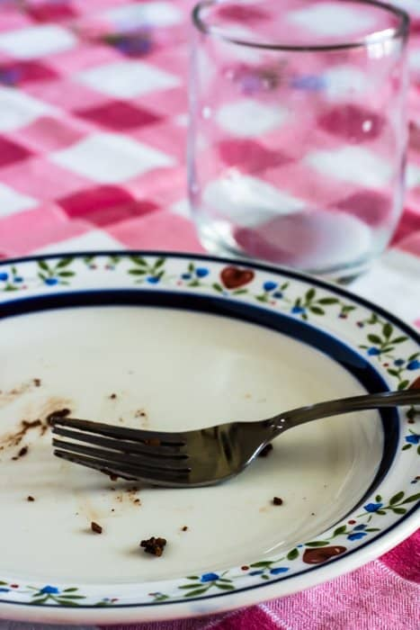 Image of empty plate with cake crumbs, plus an empty glass that had been filled with milk