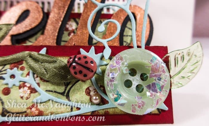 "A glittered button, a ladybug bee and a tiny glass leaf on the front ""step"" of my side step card"