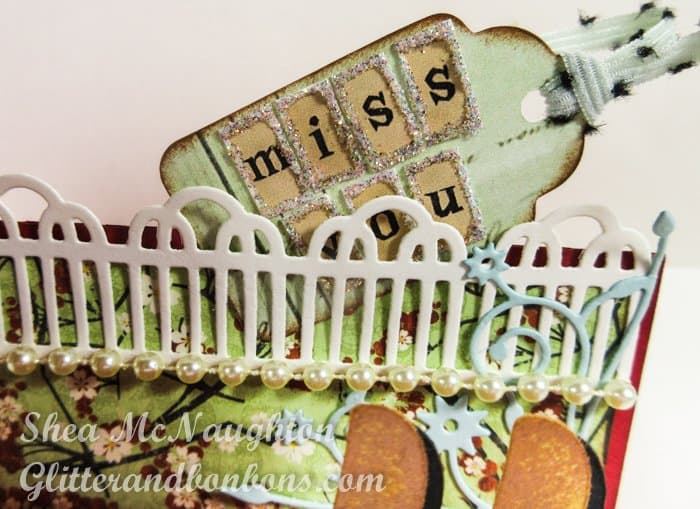 "The back ""step,"" decorated with a picket fence die cut and a tiny tag"