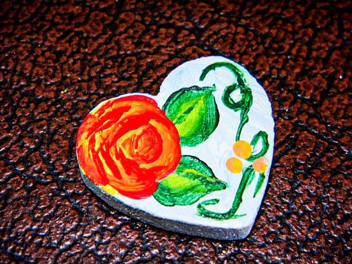 A tiny, 1-inch wooden heart painted with a matching rose