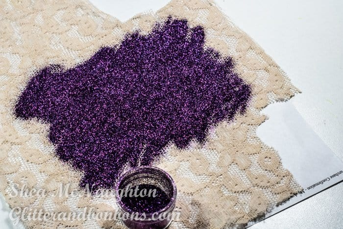 The first color of glitter poured onto the lace stencil