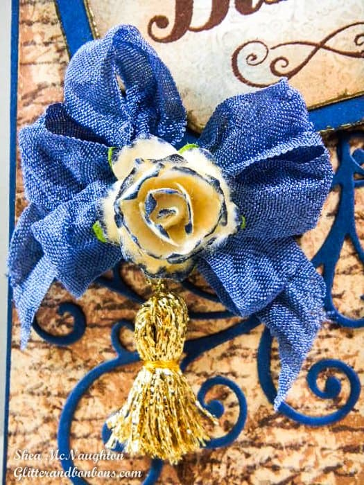 Close up of blue messy bow, custom colored paper rose, and a custom made gold tassel - lots of color and texture here