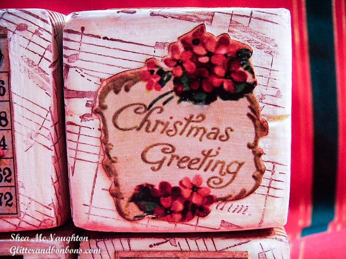 Close up of a vintage Christmas block with decoupaged image over stamped background