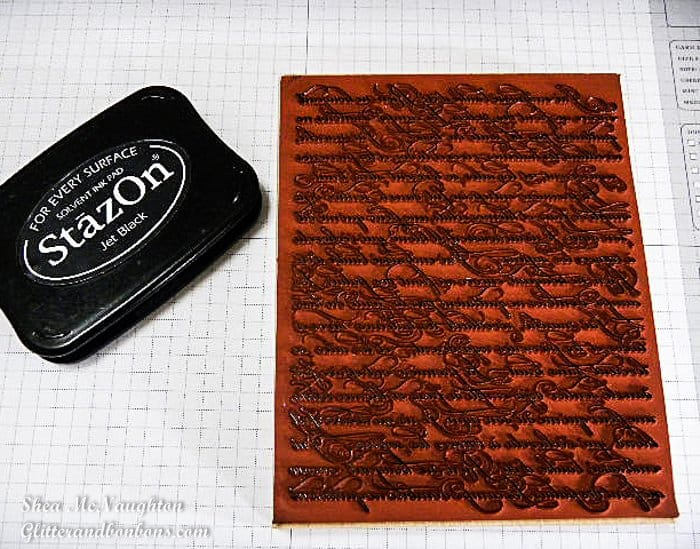 A fine script background stamp inked up with Staz On black ink