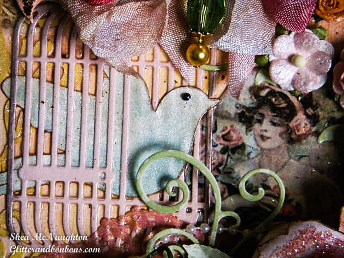 Closeup of bird die coming through birdcage die on mixed on floral mixed media project