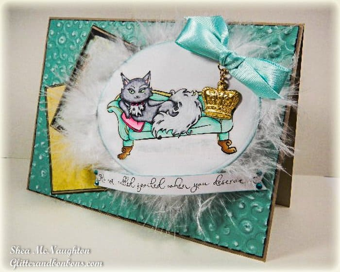 Card with embossed background, stamped cat image colored with Copics and surrounded with feathers