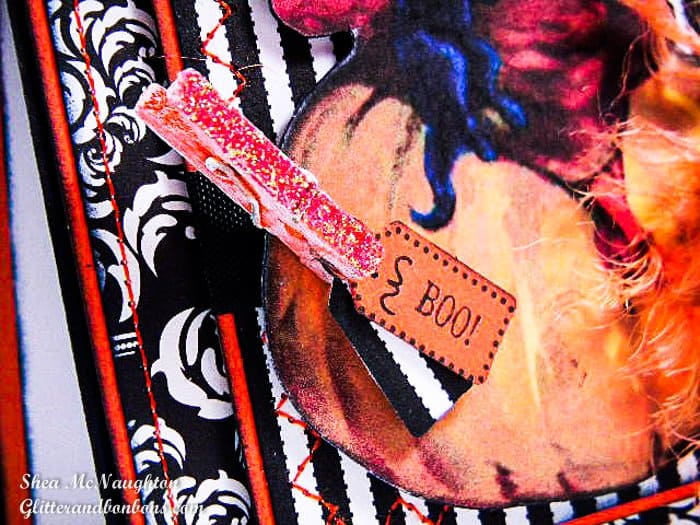 """A tiny, glittered orange clothespin hold a tiny tag with the word """"Boo"""" on it. There are plenty of patterns and textures on this card."""