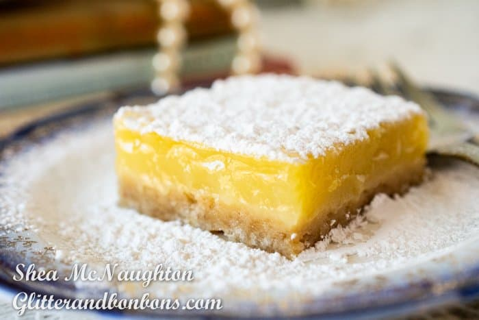 Close up of a lemon bar with powdered sugar topping