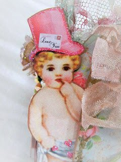 The Cupid image with glitter accents partially tucked behind a base heart