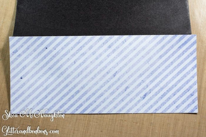 Attaching the strip of designer paper to the envelope flap