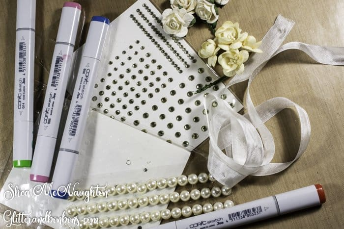 Paper art embellishments, including pearls rhinestones, seam binding and flowers, all white waiting to be custom colored