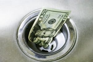The appearance of paper money going down the drain