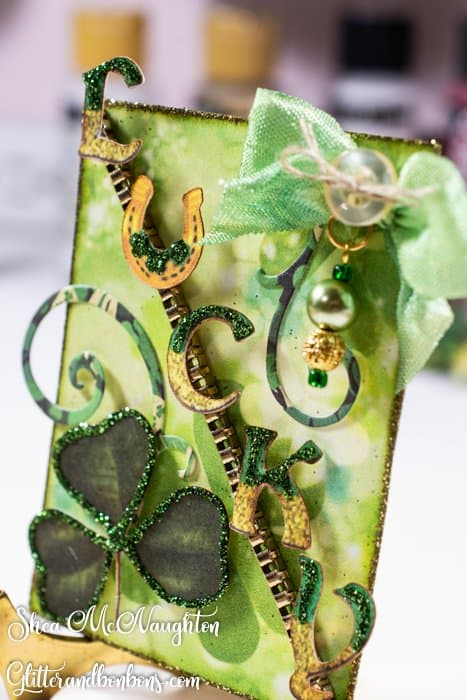 """The individual letters on this ATC spell """"LUCKY."""" They're set on a piece of gold chain and accented with a hand-dyed seam binding bow with a hand-crafted pearl charm"""