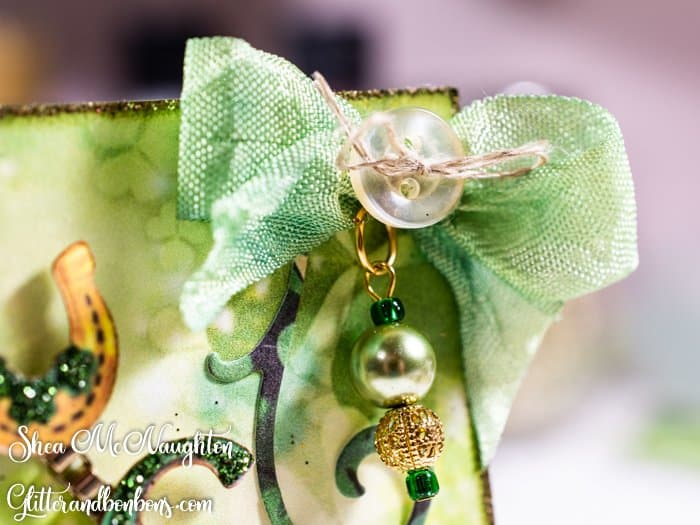 A squashy bow made with hand-dyed seam binding finished with a vintage button and a handmade pearl charm