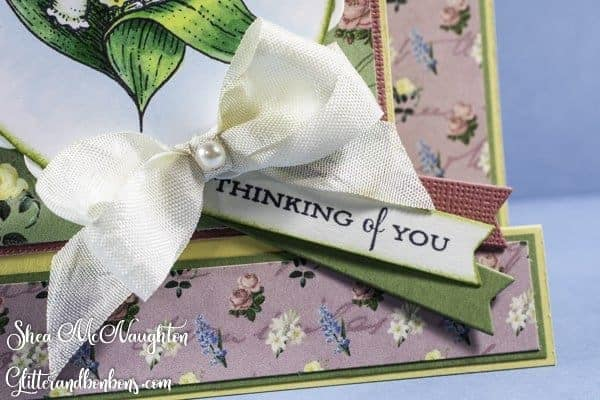 A soft bow and a pearl complete this floral card