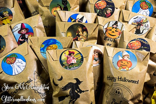 Small stamped paper bags of candy sealed with printable Halloween stickers