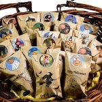 Basket of stamped treat bags with printable Halloween stickers sealing them closed