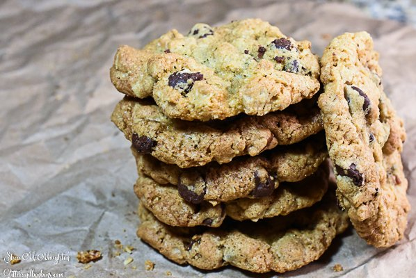 Stack of cowboy cookies with one laying against the stack